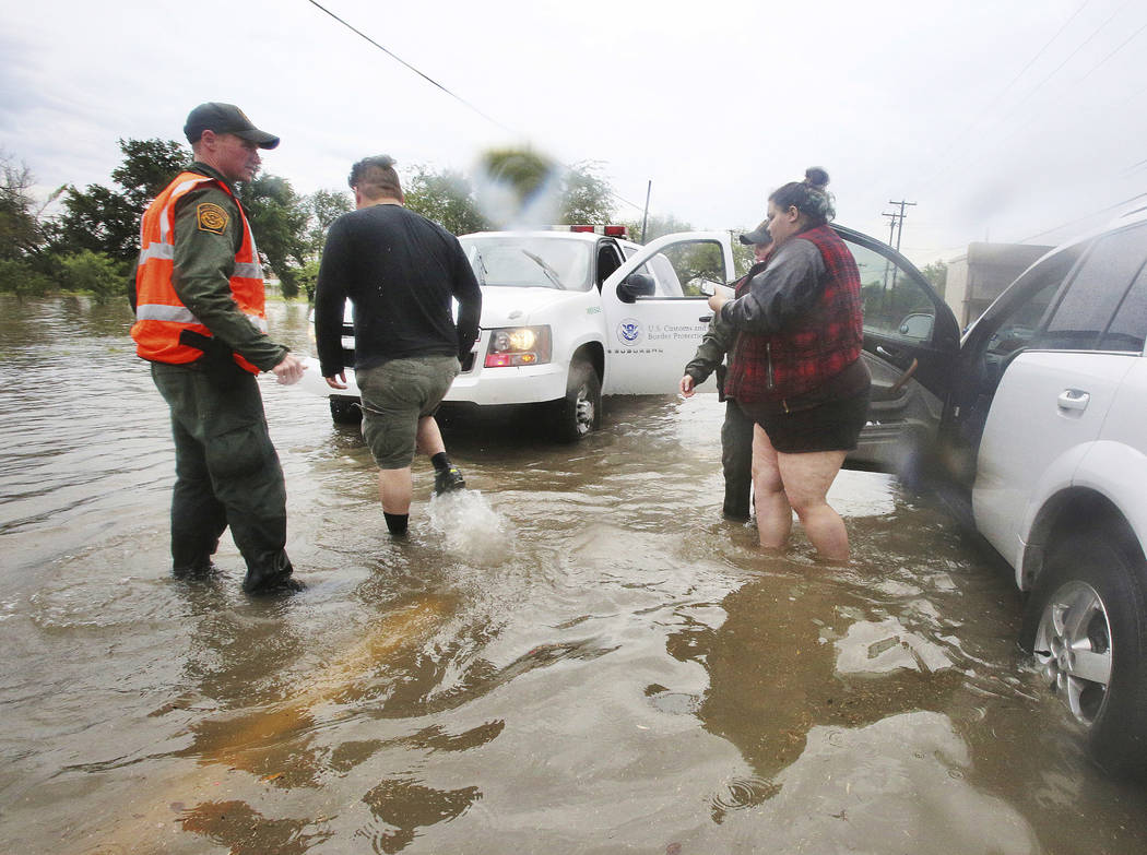 U.S. Border Patrol agents help a stranded motorist after heavy rains caused water to rise and flood whole neighborhoods, Thursday, June 21, 2018, in Mission, Texas. (Joel Martinez/The Monitor via AP)
