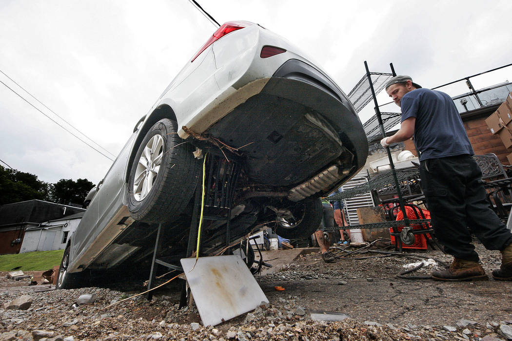 A car is supported by a single lounge stool in Bethel Park, Pa., Thursday, June 21, 2018, as clean up begins after heavy rains the night before caused severe flooding. (Gene J. Puskar/AP)