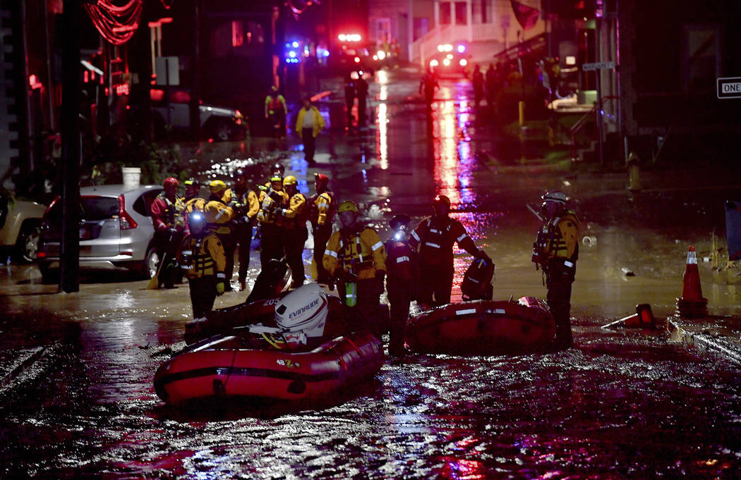 In this Wednesday, June 20, 2018, photo crews work in flood waters on Baldwin Street in Bridgeville, Pa. Strong storms containing heavy rains have caused severe flooding in parts of western Pennsy ...