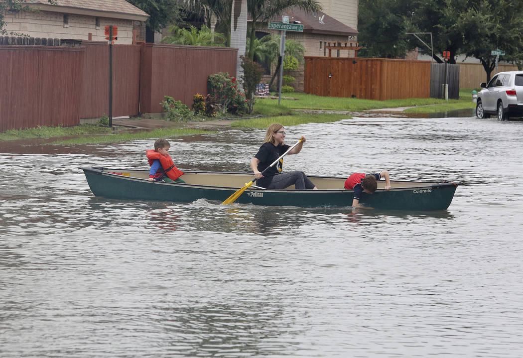 Residents use a canoe to paddle through high water after heavy rains caused water to rise and flood whole neighborhoods on Thursday, June 21, 2018, in McAllen, Texas. (Joel Martinez/The Monitor vi ...