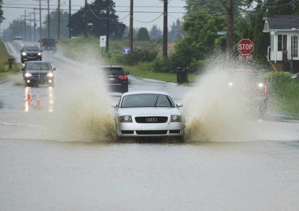 Vehicles drive through rising water along Hollywood Road in St. Joseph, Mich., Thursday, June 21, 2018, after strong storms dumped several inches of rain in Southwest Michigan. A third county in M ...
