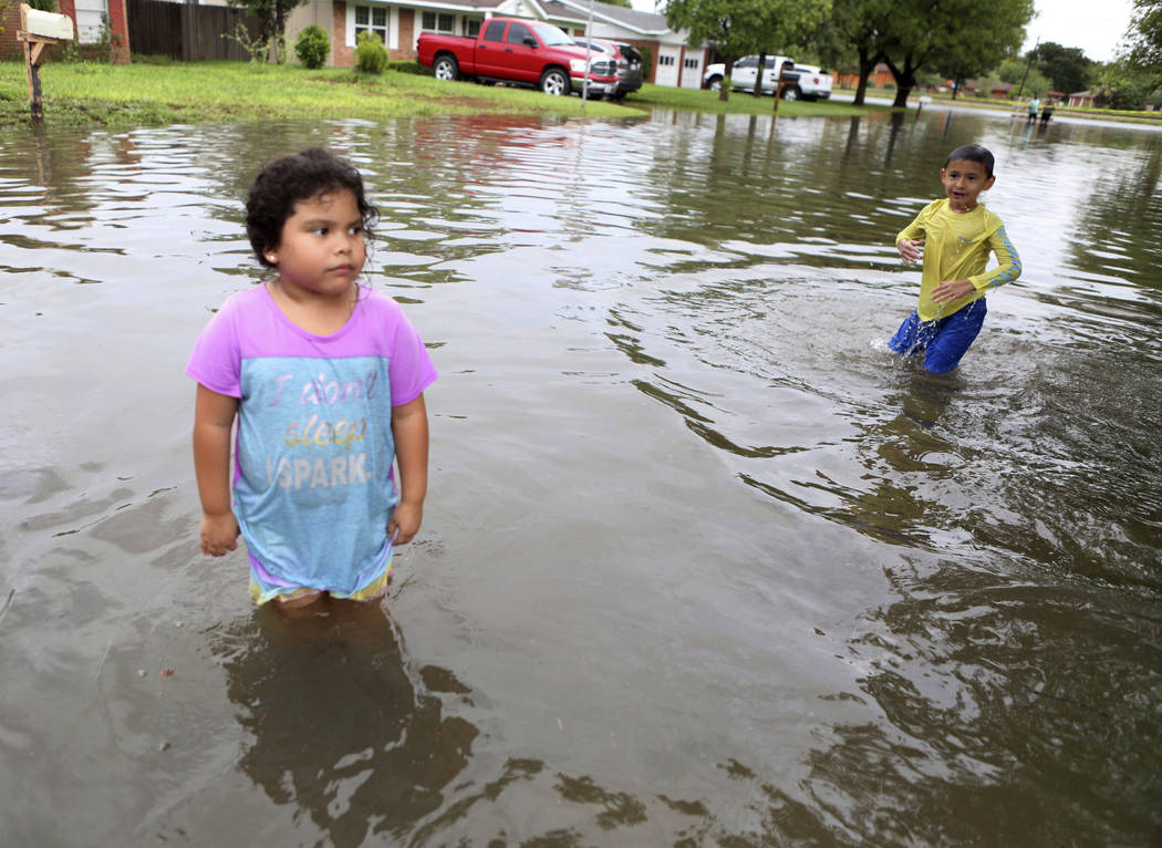 Ariana Torres, 4, and Jose Pena, 6, play in the water on their street near McAllen High School after heavy rains caused water to rise and flood neighborhoods on Thursday, June 21, 2018, in McAllen ...