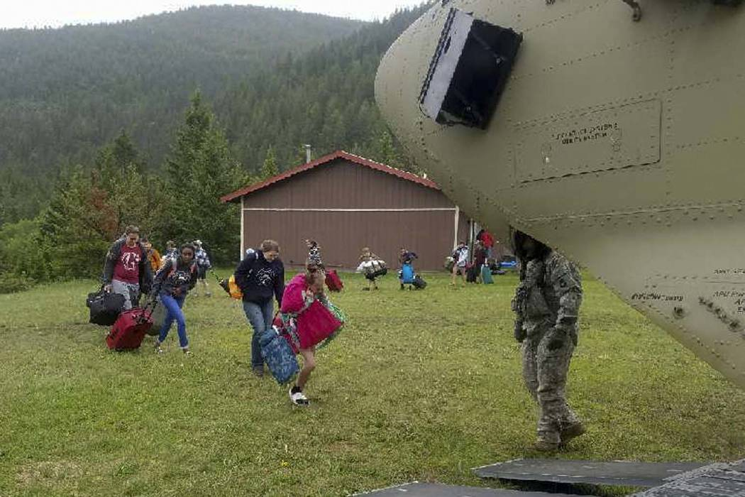 Middle school students attending a Bible camp at the Montana Wilderness School of the Bible along the Rocky Mountain Front are guided onto a Chinook helicopter Thursday, June 21, 2018. The campers ...