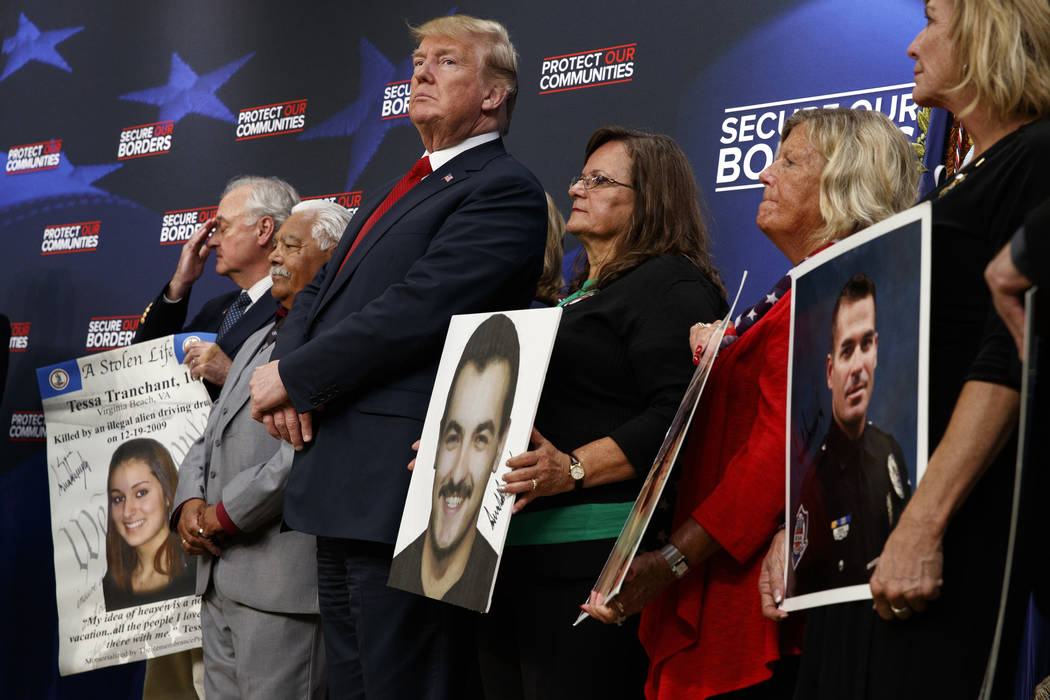 President Donald Trump stands alongside family members affected by crime committed by undocumented immigrants, at the South Court Auditorium on the White House complex, Friday, June 22, 2018, in W ...