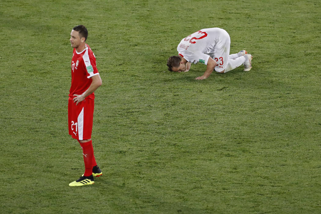 Switzerland's Xherdan Shaqiri, right, kisses the pitch next to Serbia's Nemanja Matic after scoring his side's second goal during the group E match between Switzerland and Serbia at the 2018 socce ...