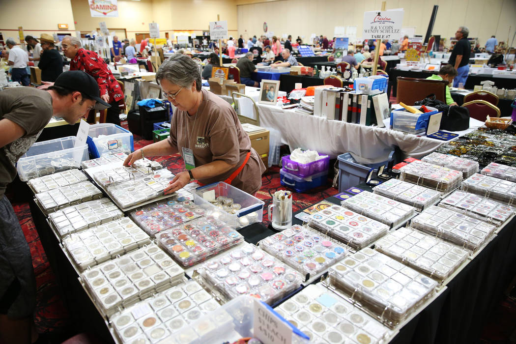 Wendy Schultz of Henderson, Nev., shows her chip collection to Jeremy Bryant of Los Angeles during the Casino Chip & Gaming Token Collectors Club annual convention at the South Point casino-ho ...
