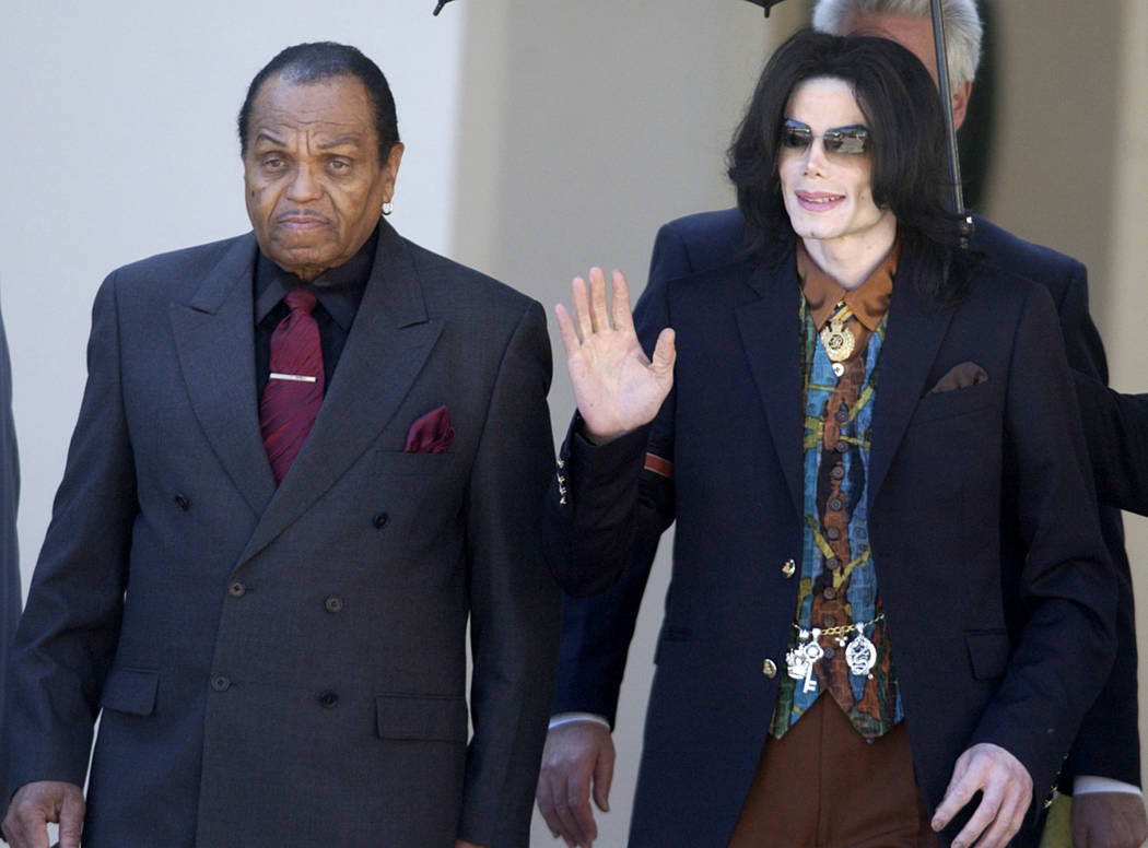 Pop star Michael Jackson leaves the Santa Barbara County Courthouse with his father, Joe, left, in Santa Maria, Calif., following a day of testimony in Jackson's trial on charges of child molestat ...
