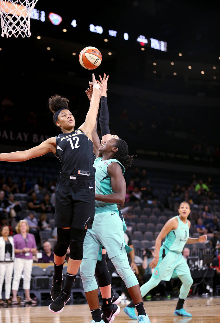 Las Vegas Aces forward Nia Coffey (12) goes up for a rebound over New York Liberty center Tina Charles (31) in the first half of a WNBA basketball game at the Mandalay Bay Events Center in Las Veg ...