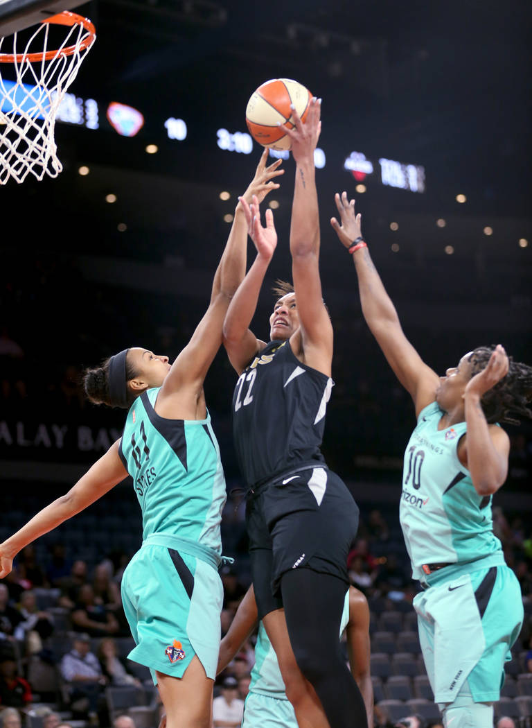 Las Vegas Aces center A'ja Wilson (22) goes up for a shot between New York Liberty center Kiah Stokes (41) and New York Liberty guard Epiphanny Prince (10) in the first half of a WNBA basketball g ...