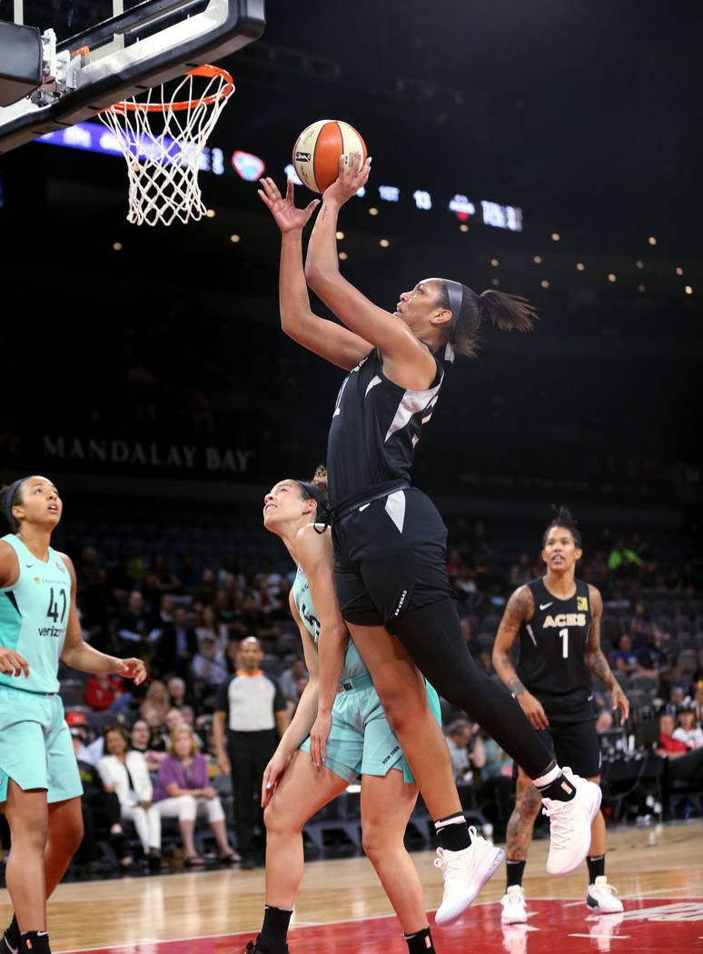 Las Vegas Aces center A'ja Wilson (22) goes up for shot over New York Liberty guard Kia Nurse (5) in the first half of a WNBA basketball game at the Mandalay Bay Events Center in Las Vegas on Sund ...