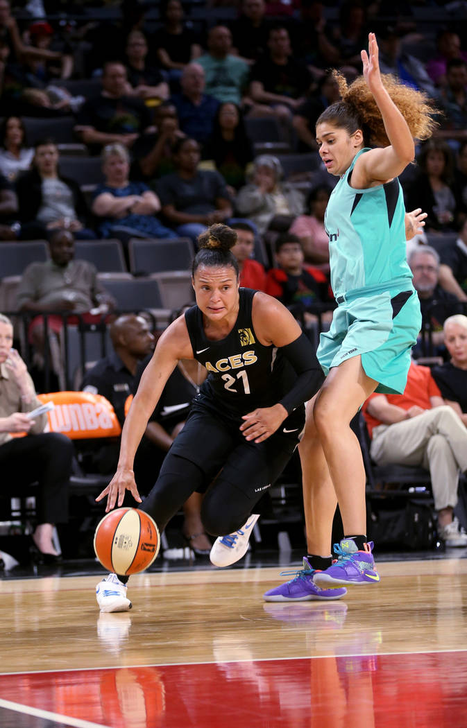 Las Vegas Aces guard Kayla McBride (21) drives past New York Liberty center Amanda Zahui B. (17) in the second half of a WNBA basketball game at the Mandalay Bay Events Center in Las Vegas on Sund ...