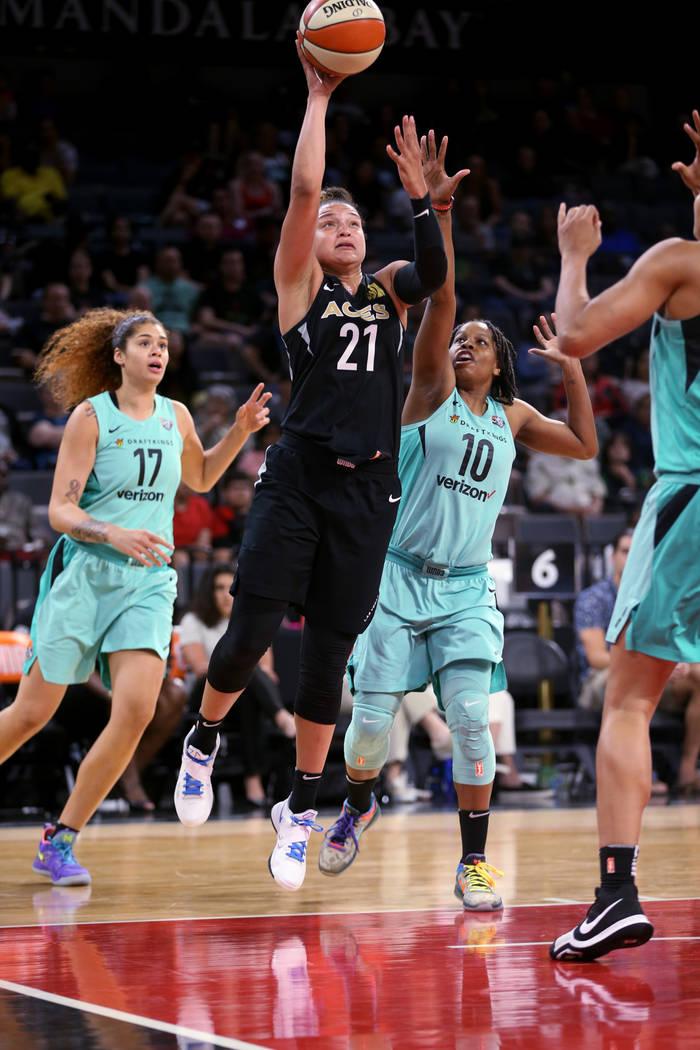 Las Vegas Aces guard Kayla McBride (21) shoots between New York Liberty center Amanda Zahui B. (17) and guard Epiphanny Prince (10) in the second half of a WNBA basketball game at the Mandalay Bay ...