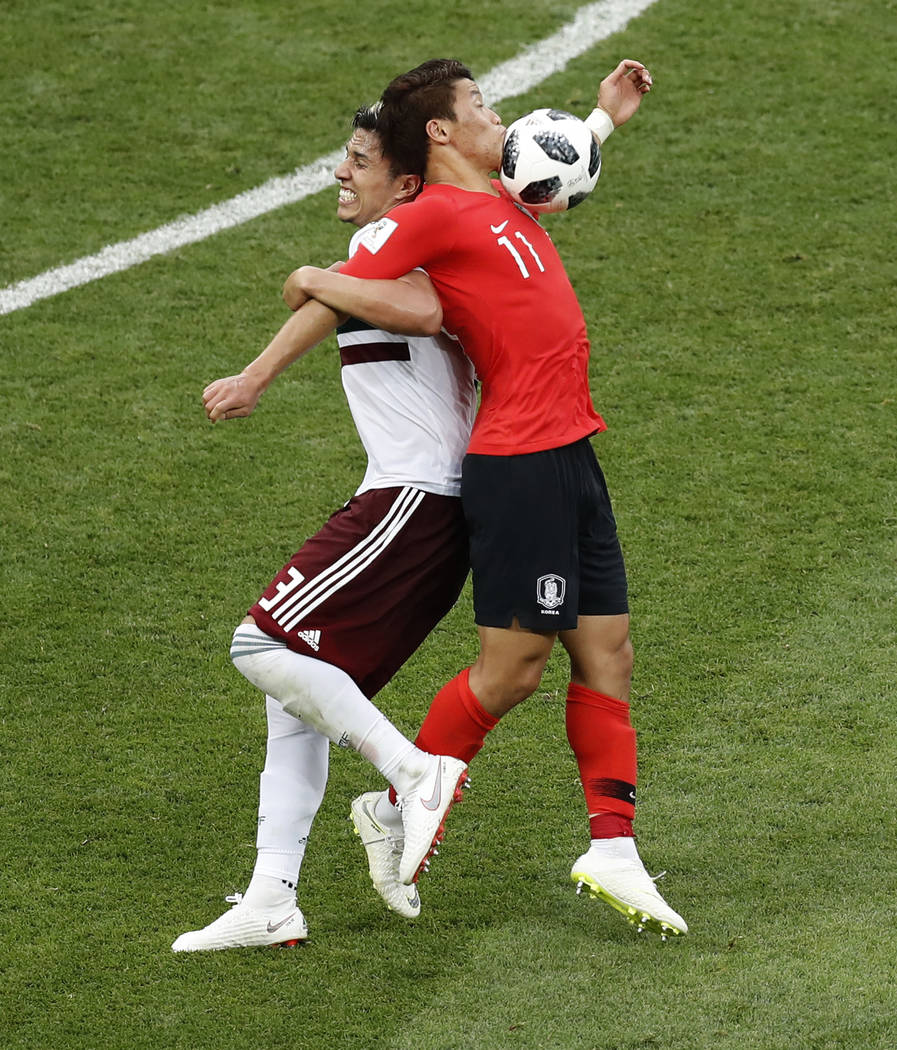 South Korea's Hwang Hee-chan attempts to control the ball as he is challenged by Mexico's Carlos Salcedo, left, during the group F match between Mexico and South Korea at the 2018 soccer World Cup ...