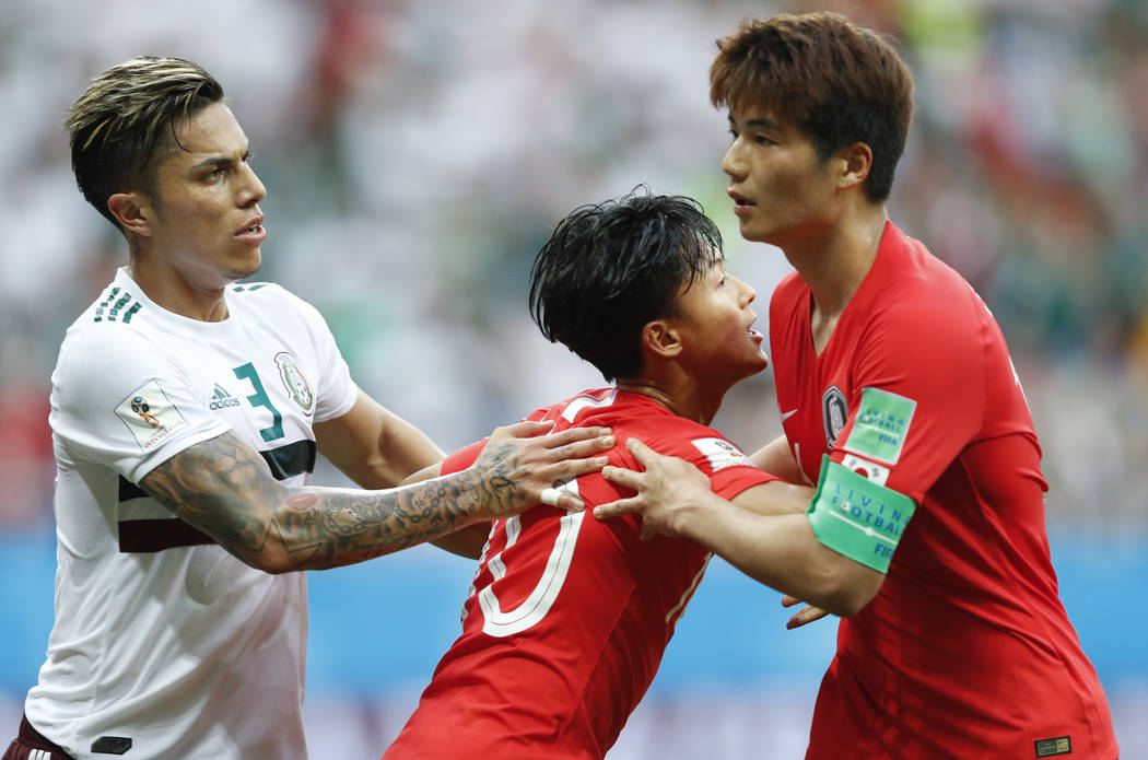 South Korea'sLeeSeung-woo, center= hols teammate Ki Sung-yueng as Mexico's Carlos Salcedo stands beside during the group F match between Mexico and South Korea at the 2018 soccer World ...