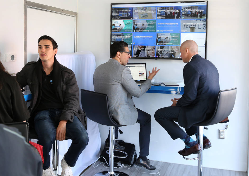 Francisco Martinez, center, VP of social media at Zen Media, discusses with Ryan Woodward, right, Chase's business area manager, at the Chase for Business BizMobile, a 27-foot advice center on whe ...