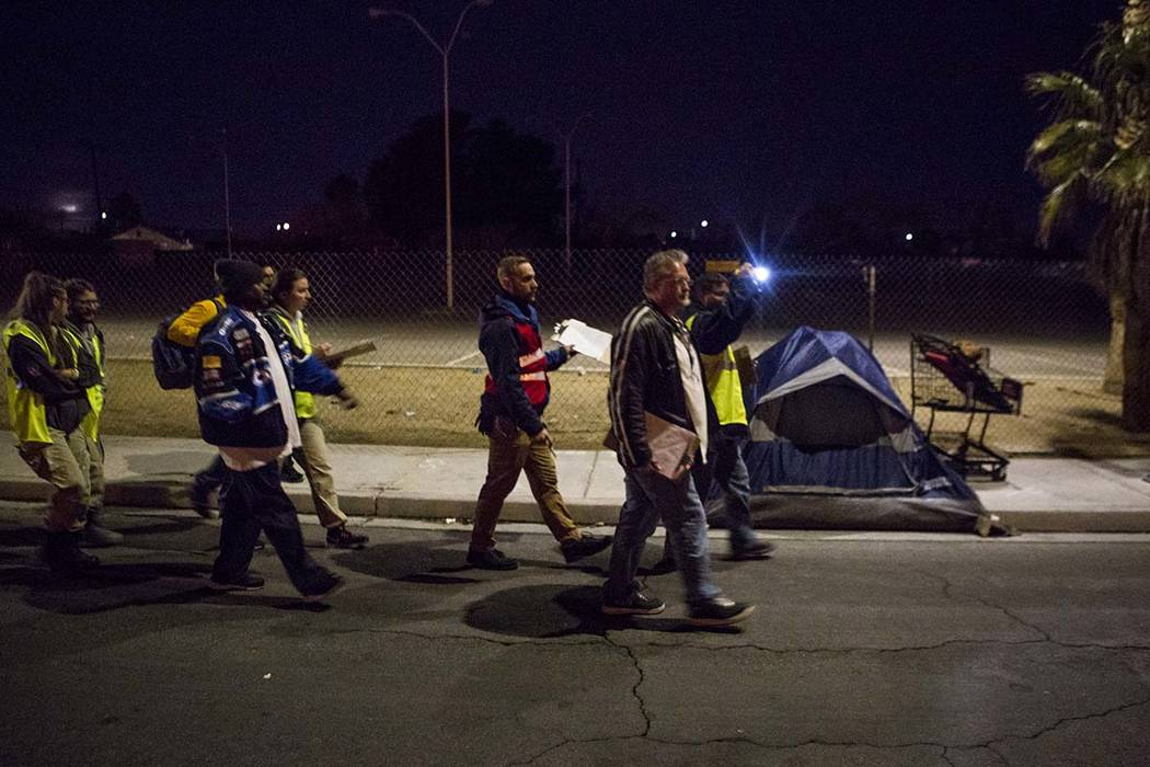Volunteers for Clark County's annual homeless census walk past an encampment on Veterans Memorial Drive in Las Vegas during Clark County's annual homeless census early in the morning on Thursday, ...