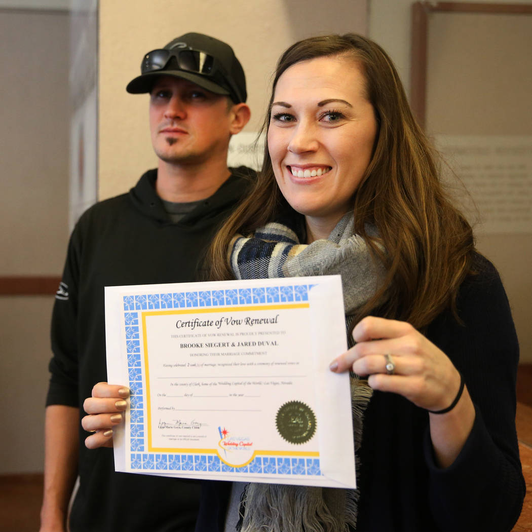 Jared Duval, left, and his wife Brooke Siegert, of Still Water, Minn., receive their wedding vow renewal certificate at the Marriage License Bureau in Las Vegas, Thursday, Jan. 3, 2019. Duval and ...