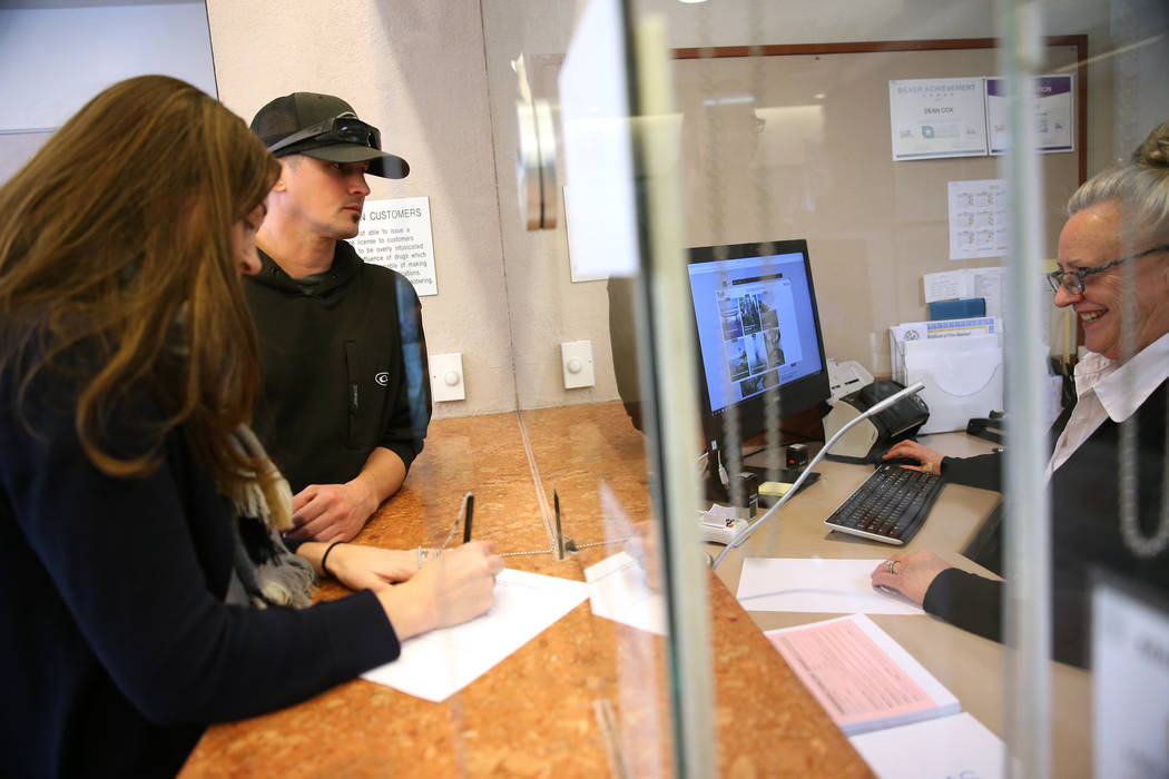 Jared Duval, center, and his wife Brooke Siegert, of Still Water, Minn., apply for their wedding vow renewal certificate with office specialist Rebecca Neff, at the Marriage License Bureau in Las ...