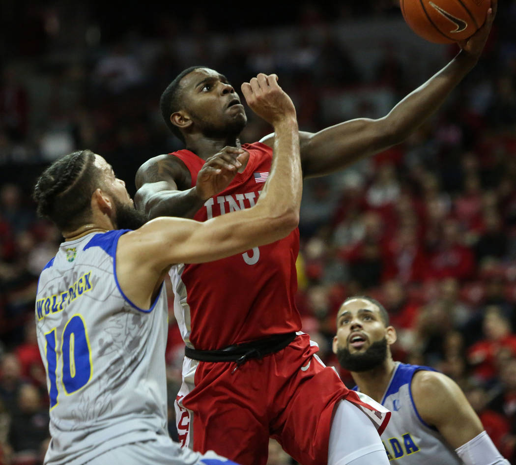 UNLV Rebels guard Amauri Hardy (3) takes a shot while under pressure from Nevada Wolf Pack forward Caleb Martin (10) during the second half of a basketball game at the Thomas & Mack Center in ...