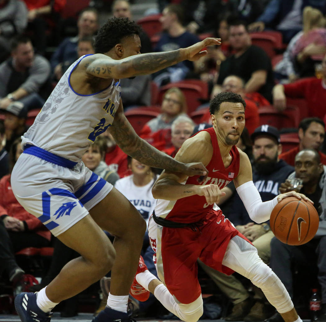 UNLV Rebels guard Noah Robotham (5) run with the ball while under pressure from Nevada Wolf Pack forward Jordan Caroline (24) during the second half of a basketball game at the Thomas & Mack C ...