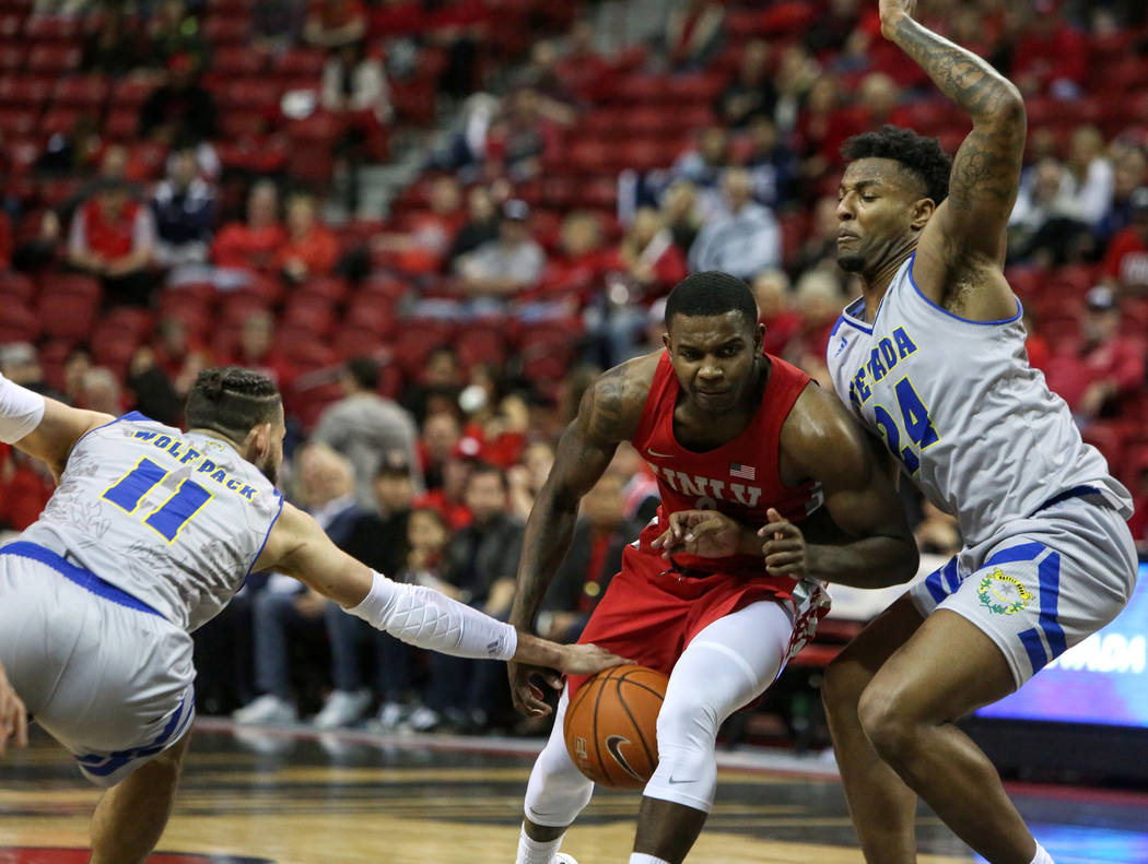 Nevada Wolf Pack forward Cody Martin (11) steals the ball from UNLV Rebels guard Amauri Hardy (3) as he is guarded by Nevada Wolf Pack forward Jordan Caroline (24) during the second half of a bask ...