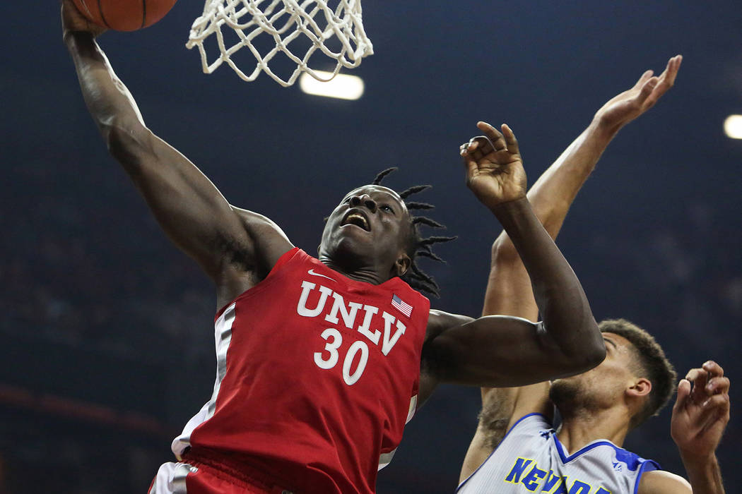 UNLV Rebels forward Jonathan Tchamwa Tchatchoua (30) takes a shot while under pressure from Nevada Wolf Pack forward Trey Porter (15) during the first half of a basketball game at the Thomas & ...