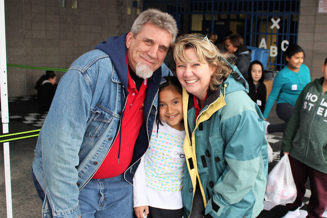 Volunteer Rick Lefever and Nikki Berti pose with a child. (Goodie Two Shoes Foundation)