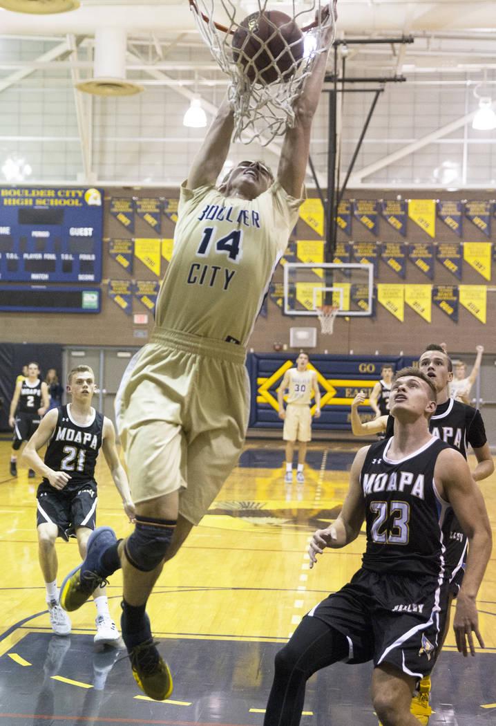 Boulder City senior guard Karson Bailey (14) dunks over Moapa Valley senior forward Derek Reese (23) in the first quarter on Tuesday, Jan. 29, 2019, at Boulder City High School, in Las Vegas. (Ben ...