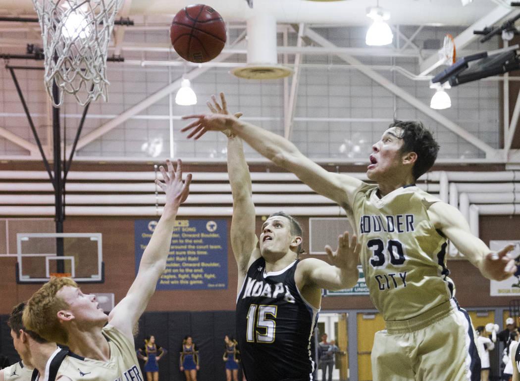 Moapa Valley senior forward Jessup Lake (15) shoots over Boulder City sophomore forward Ethan Speaker (30) and sophomore guard Matt Morton (24) in the second quarter on Tuesday, Jan. 29, 2019, at ...