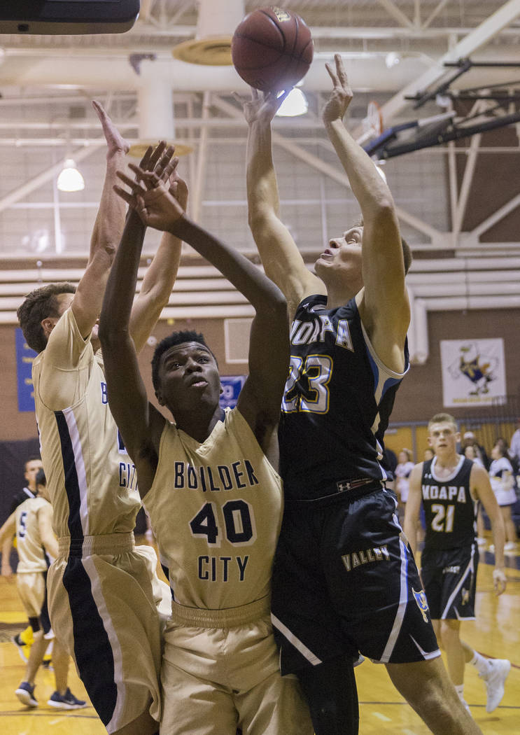 Moapa Valley senior forward Derek Reese (23) fights for a rebound with Boulder City junior forward Jacob Sanford (40) in the second quarter on Tuesday, Jan. 29, 2019, at Boulder City High School, ...