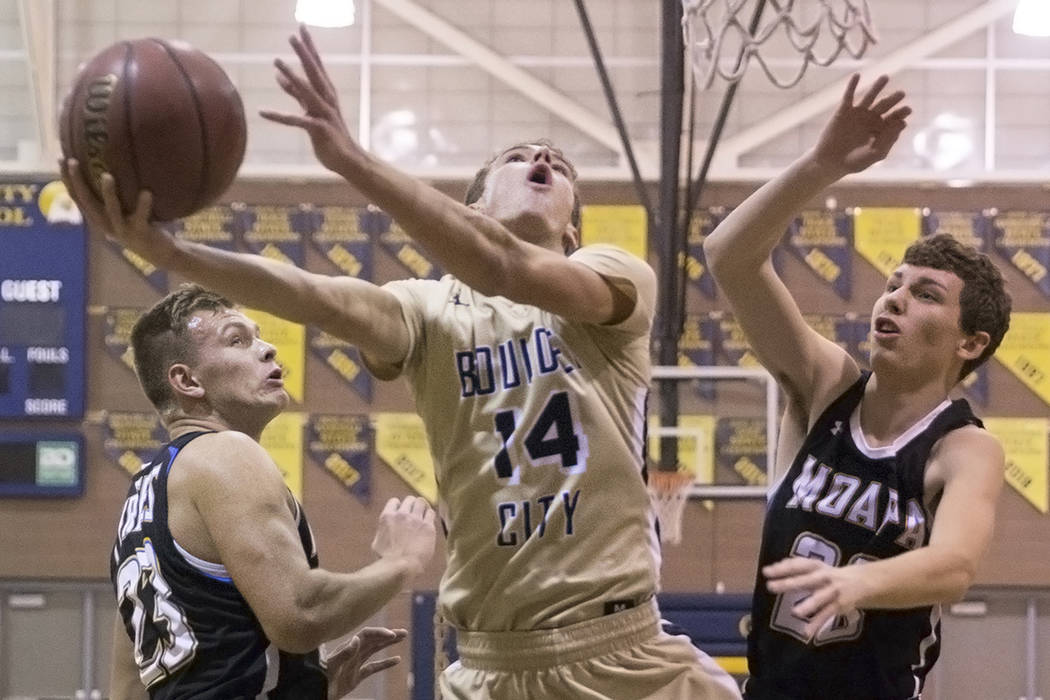 Boulder City senior guard Karson Bailey (14) slices to the rim past Moapa Valley sophomore forward Cameron Reese (25) and senior forward Derek Reese (23) in the first quarter on Tuesday, Jan. 29, ...