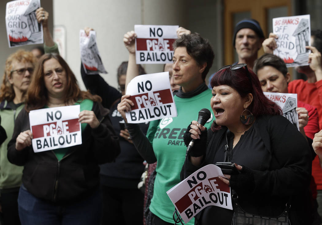 Jessica Tovar, right, speaks at a rally before a California Public Utilities Commission meeting in San Francisco, Monday, Jan. 28, 2019. California regulators have approved a measure allowing Paci ...