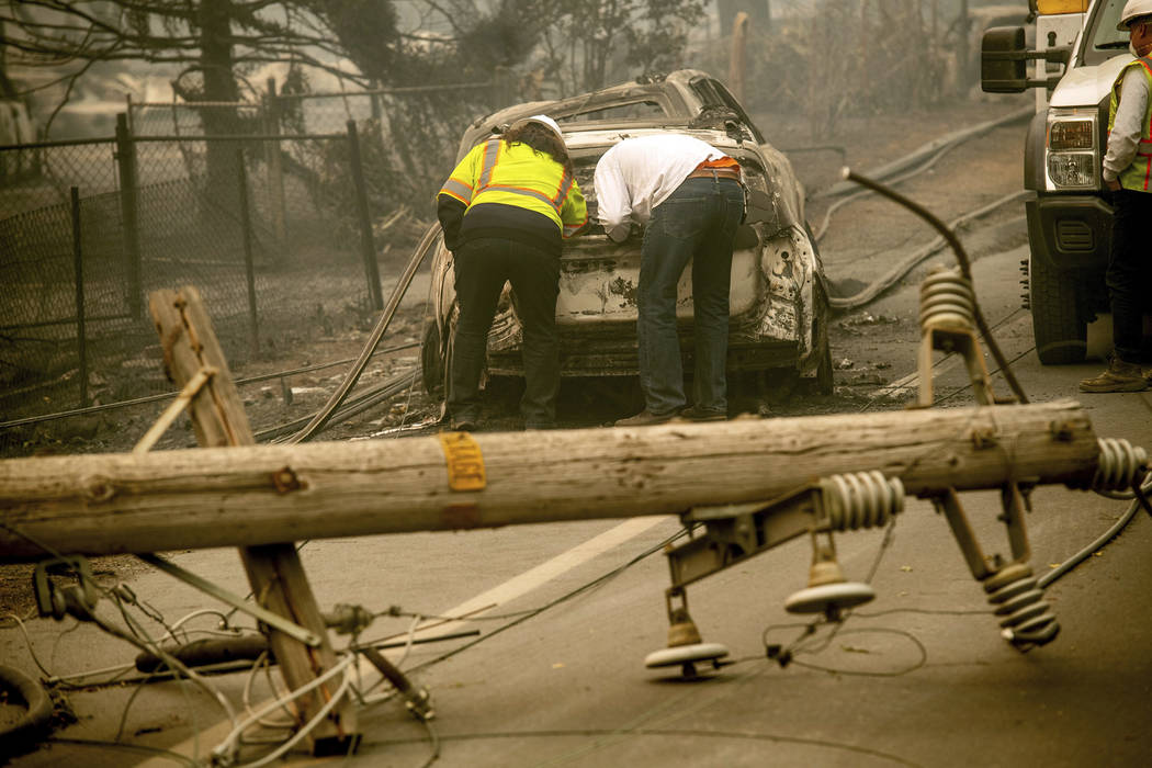 FILE - In this Nov. 10, 2018 file photo, with a downed power utility pole in the foreground, Eric England, right, searches through a friend's vehicle after the wildfire burned through Paradise, Ca ...