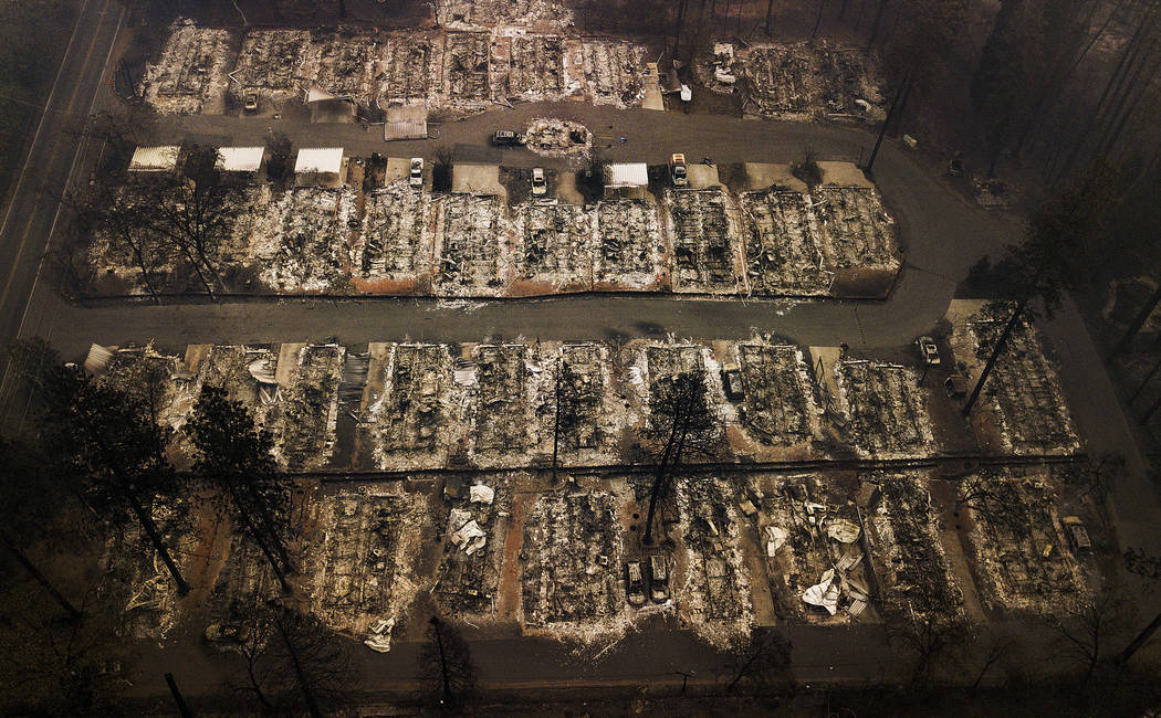 FILE - This Nov. 15, 2018, aerial file photo shows the remains of residences leveled by the Camp wildfire in Paradise, Calif. Pacific Gas & Electric Corp. is expected to file for bankruptcy pr ...
