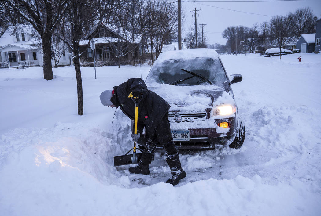 Adam Fischer shovels out his vehicle to go to work Monday, Jan. 28, 2019, in Rochester, Minn. Heavy snow and gusting winds created blizzard-like conditions Monday across parts of the Midwest, prom ...