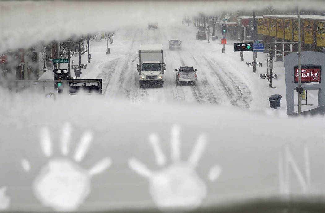 Hand prints are left behind as traffic moves slowly along College Avenue during a snowstorm Monday, Jan. 28, 2019, in downtown Appleton, Wis. (Dan Powers/The Post-Crescent via AP)
