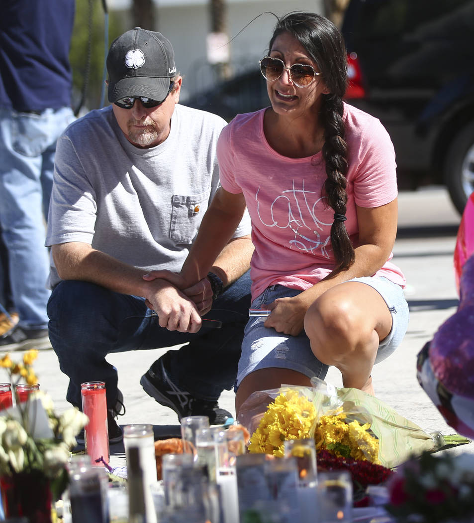 Mike and Jessica Yerkey of Ramona, Calif., pause at a memorial at Las Vegas Boulevard and Sahara Avenue in Las Vegas during the early hours of Tuesday, Oct. 3, 2017. Chase Stevens Las Vegas Review ...