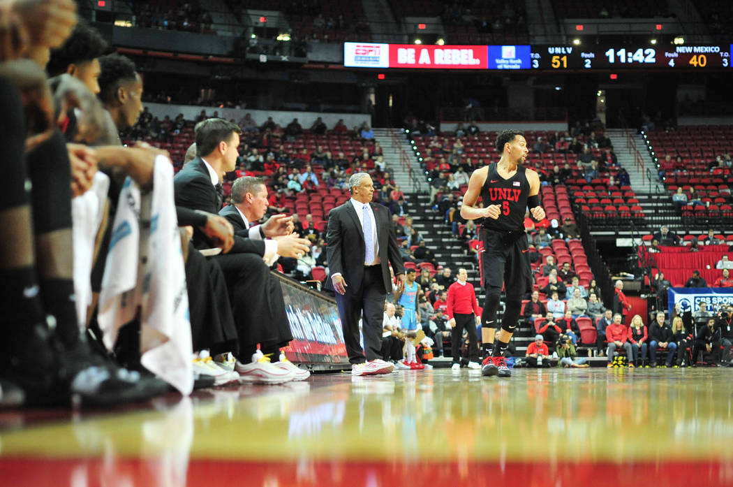 UNLV Rebels head coach Marvin Menzies, center, walks the sidelines as UNLV guard Noah Robotham (5) jogs past during the second half of the UNLV Rebels and the New Mexico Lobos NCAA basketball game ...