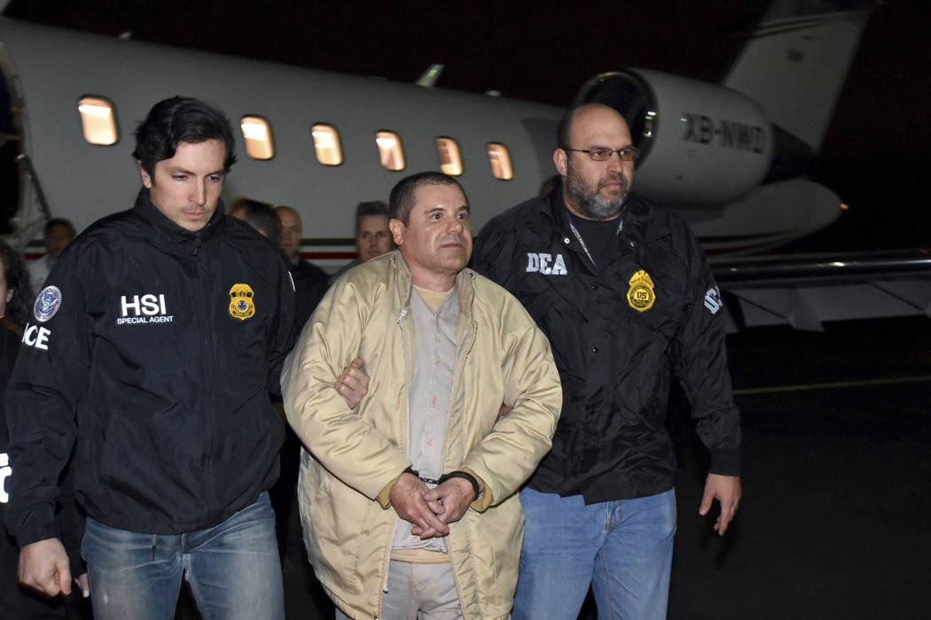 """In this Jan. 19, 2017 file photo provided U.S. law enforcement, authorities escort Joaquin """"El Chapo"""" Guzman from a plane to a waiting caravan of SUVs at Long Island MacArthur Airport, in Ronkonko ..."""