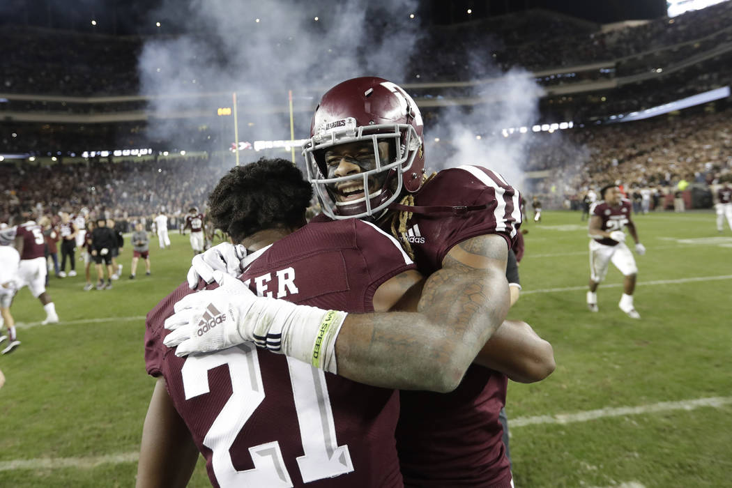 In this Nov. 24, 2018, file photo, Texas A&M wide receiver Kendrick Rogers, right, celebrates with Charles Oliver (21) after their 74-72 win in seven overtimes against LSU in an NCAA college footb ...