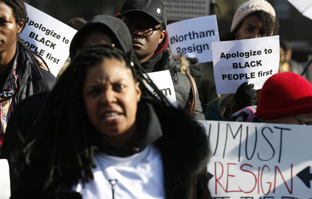 Demonstrators hold signs and chant outside the Governors Mansion at the Capitol in Richmond, Va., Saturday, Feb. 2, 2019. The demonstrators are calling for the resignation of Virginia Governor Ral ...