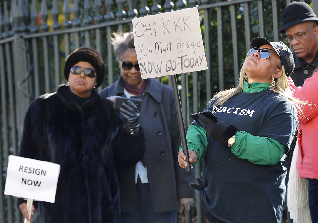 Tara Raigns, of Petersburg, Va., right, reacts to Gov. Ralph Northam's comments during a news conference in the Governor's Mansion in Richmond, Va., on Saturday, Feb. 2, 2019. She joined protester ...