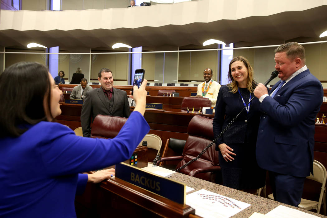 Marc McDermont serenades his wife, Shea Backus, D-Las Vegas, as Assemblywoman Rochelle Nguyen, D-Las Vegas takes a photo in the Legislative Building in Carson City on the first day of the 80th ses ...
