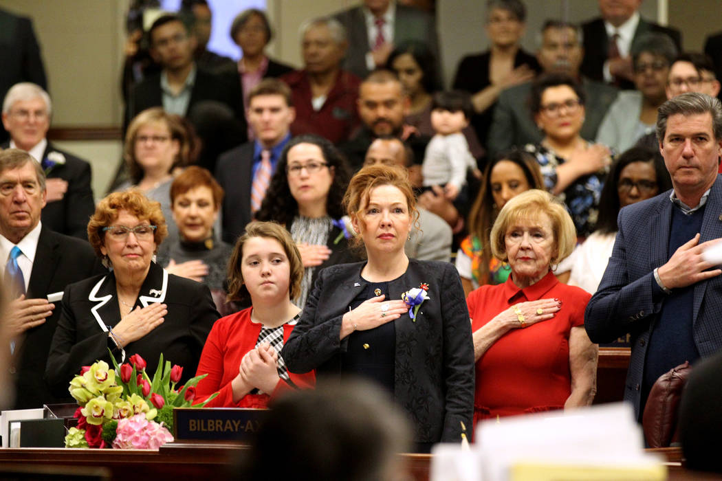 Assembly members and guests, including Assemblywoman Shannon Bilbray-Axelrod, D-Las Vegas, center, stand during the presentation of the colors in the Legislative Building in Carson City on the fir ...