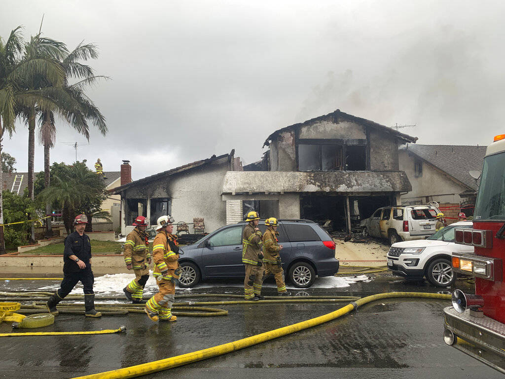 Firefighters respond to the scene of a plane crash at a home in Yorba Linda, Calif., Sunday, Feb. 3, 2019. A twin-engine Cessna 414A crashed in Yorba Linda shortly after taking off from the nearby ...