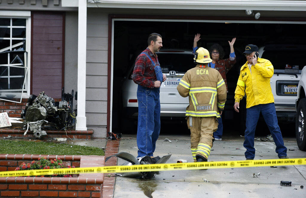 Residents work with authorities at the scene of a deadly plane crash in the residential neighborhood of Yorba Linda, Calif., Sunday, Feb. 3, 2019. The Federal Aviation Administration said a twin-e ...