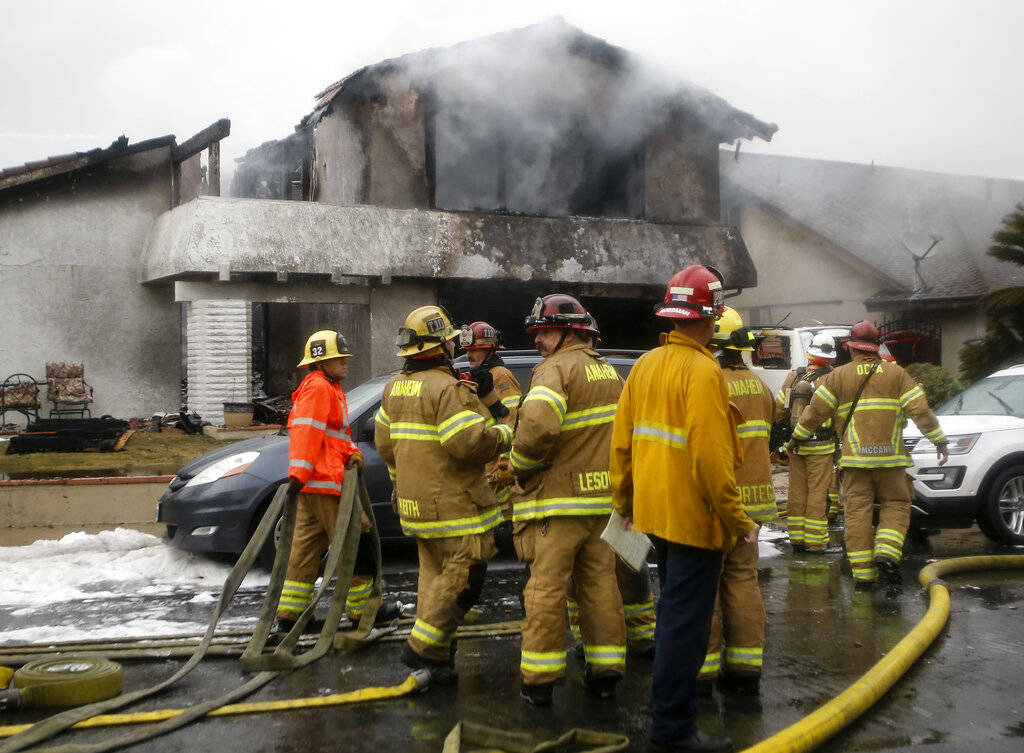 Firefighters suppress a fire at the scene of a deadly plane crash in the residential neighborhood of Yorba Linda, Calif., Sunday, Feb. 3, 2019. The Federal Aviation Administration said a twin-engi ...