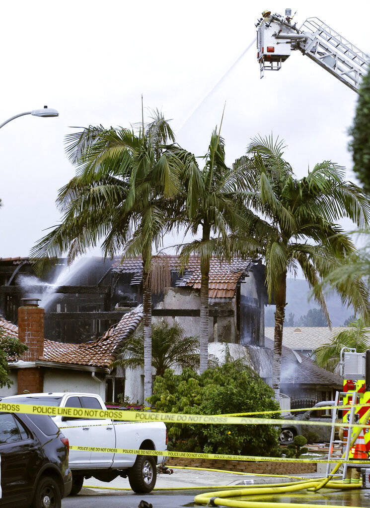 Firefighters work the scene of a deadly plane crash in the residential neighborhood of Yorba Linda, Calif., Sunday, Feb. 3, 2019. The Federal Aviation Administration said a twin-engine Cessna 414A ...