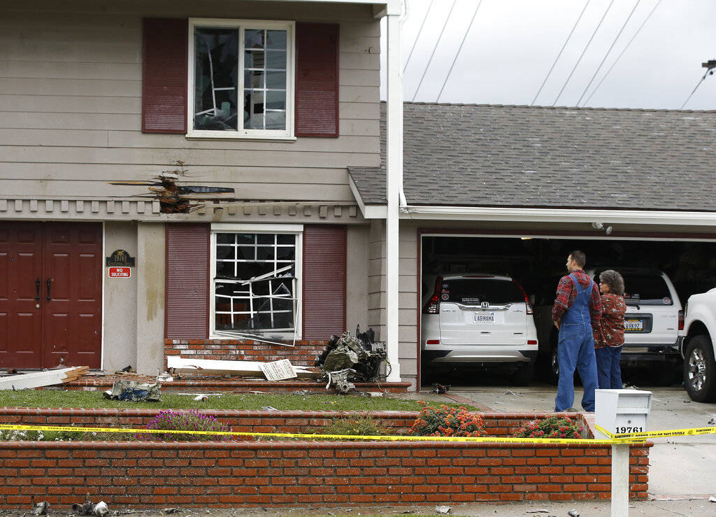 Residents look at the debris that hit their home after a small plane crashed into the residential neighborhood of Yorba Linda, Calif., Sunday, Feb. 3, 2019. A few people died and a few others were ...
