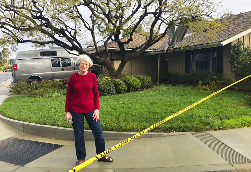 Catherine Paulson, 78, stands in front of her Yorba Linda, Calif., home that has a piece of aircraft wreckage piercing the roof Monday, Feb. 4, 2019. She said she wasn't home when the plane went d ...